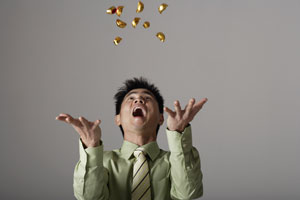 man throwing gold into the air - Asia Images Group