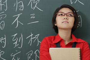 woman looking up in front of chinese characters written in chalk - Asia Images Group