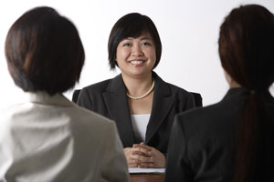 business woman sitting at desk smiling - Asia Images Group