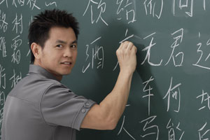 man writing Chinese characters on chalk board - Asia Images Group