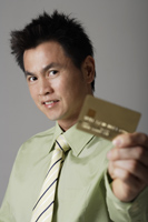 man smiling behind gold credit card - Asia Images Group