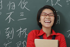 woman laughing in front of Chinese characters written on chalk board - Asia Images Group