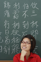 woman standing in front of chinese characters written in chalk - Asia Images Group
