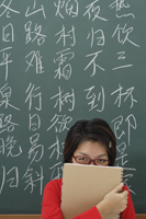 student hiding behind notepad in front of chinese characters written on chalk board - Asia Images Group
