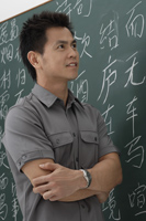 man standing in front of Chinese characters written on chalk board - Asia Images Group