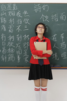 student standing in front of chinese characters written on chalk board - Asia Images Group