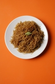 Noodles on plate on orange place mat. - Asia Images Group