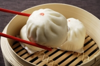red chopstick holding dim sum (bao) - Asia Images Group