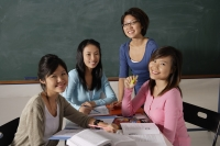 Four women studying together. - Asia Images Group