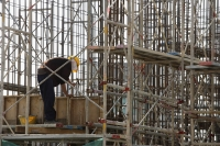 Construction worker in building frame. - Asia Images Group