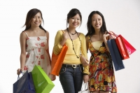 Three women holding shopping bags. - Asia Images Group