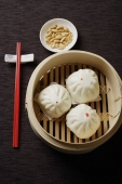 Steamed buns in bamboo steamers with red chopsticks - Asia Images Group
