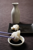 chopstick dipping dim sum in soy sauce - Asia Images Group