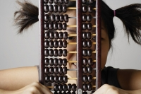 Young woman peering through abacus. - Asia Images Group