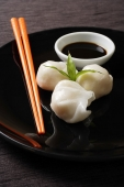 dim sum on plate with orange chopsticks - Asia Images Group