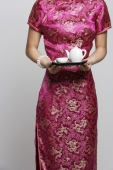 Cropped shot of woman wearing a pink cheongsam holding tea - Asia Images Group