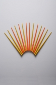 Orange and yellow chopsticks in the shape of a fan. - Asia Images Group