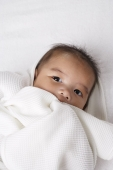 Head shot of Chinese baby wrapped up in a white blanket. - Asia Images Group