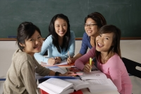 Four young women studying together and laughing. - Asia Images Group