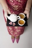 close up of woman wearing pink cheongsam holding tray with tea - Asia Images Group