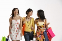 Three women carrying shopping bags. - Asia Images Group