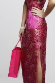 Cropped shot of woman wearing a pink cheongsam holding a shopping bag - Asia Images Group