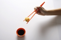 hand holding dimsum between orange chopsticks - Asia Images Group