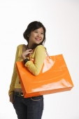 Young woman holding large shopping bag. - Asia Images Group