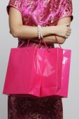 Cropped shot of woman wearing pink cheongsam carrying shopping bags. - Asia Images Group