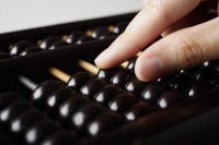 close up of hand touching abacus - Asia Images Group
