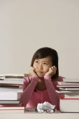 Young woman sitting at desk with books looking sad. - Asia Images Group