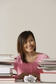 Young woman sitting at desk with books. - Asia Images Group