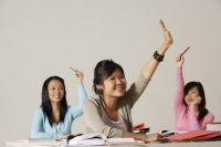 Three women raising their hands in class. - Asia Images Group