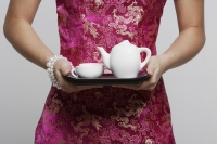 cropped shot of woman wearing pink cheongsam holding tea - Asia Images Group