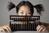 Young woman peering behind abacus. - Asia Images Group
