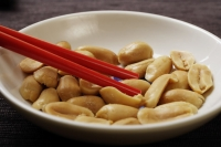 close up of red chopsticks picking up peanuts - Asia Images Group