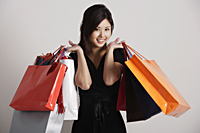 Chinese woman holding shopping bags, smiling - Asia Images Group