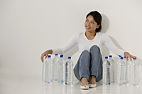 Young Asian woman sitting with water bottles - Asia Images Group