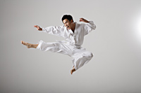 Man doing a flying kick, martial arts - Asia Images Group