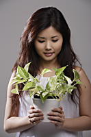 Chinese woman holding green plant - Asia Images Group