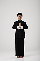 Man meditating wearing traditional Chinese clothes - Asia Images Group