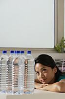 Young Asian woman looking at water bottles - Asia Images Group