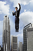 Man flying in the sky over buildings - Asia Images Group