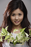 Head shot of Chinese woman holding green plant - Asia Images Group