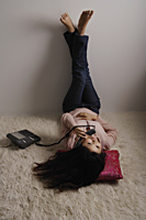 Chinese woman laying on floor, talking on phone - Asia Images Group
