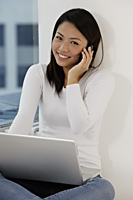 Young Asian woman talking on phone while looking at laptop - Asia Images Group