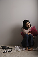 Chinese woman sitting on floor looking sad - Asia Images Group