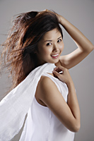Chinese woman wearing white, hair blowing - Asia Images Group