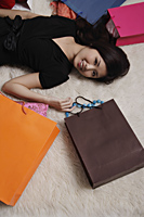 Chinese woman laying on floor with shopping bags - Asia Images Group