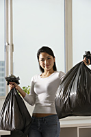 Young Asian woman holding up trash bags - Asia Images Group